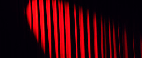 Photo of spotlight illuminating a red curtain
